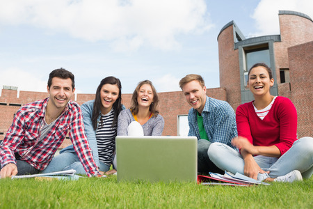 campus building: Group portrait of young students with laptop in the lawn against college building