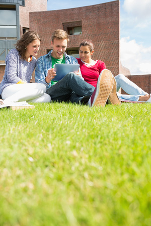 Group of young students using tablet PC in the lawn against college building photo