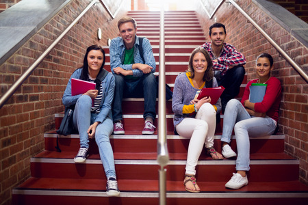 student university: Group portrait of young college students sitting on stairs in the college