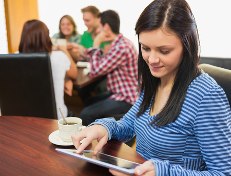Smiling female with coffee using tablet PC and students around table in background at  the coffee shop photo