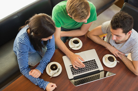 Overhead view of three students using laptop while having coffee at  the coffee shop Stock Photo