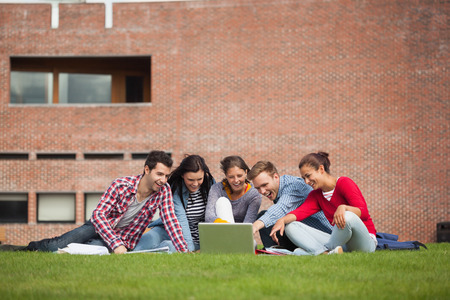 Five casual students sitting on the grass pointing at laptop on campus at college photo
