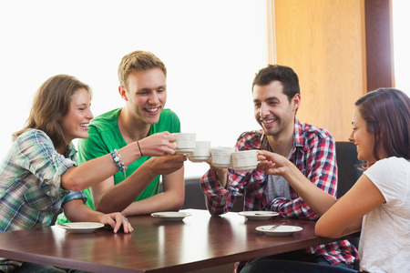 Four casual students drinking a cup of coffee in college canteen photo