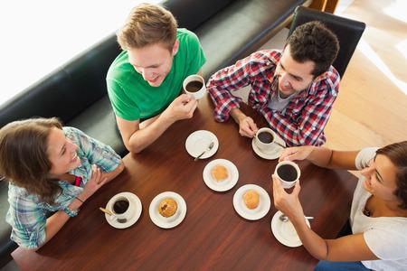 mujer tomando cafe: Cuatro estudiantes sonrientes con una taza de caf� en el chat en la cantina de la universidad
