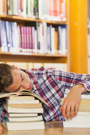 Exhausted handsome student resting head on piles of books in library photo