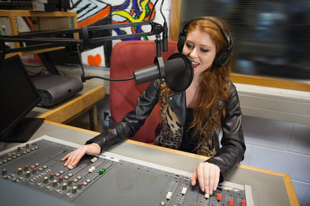 Happy beautiful radio host moderating sitting in studio at college Stok Fotoğraf