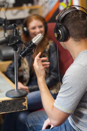Aantrekkelijke glimlachende radiopresentator interviewen een gast in de studio op de hogeschool Stockfoto