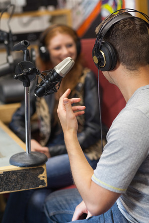 Attractive smiling radio host interviewing a guest in studio at college Stock Photo
