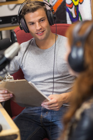 studios: Attractive happy radio host interviewing a guest holding clipboard in studio at college Stock Photo