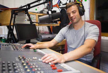 Knappe gelukkige radiopresentator matigende in studio op de hogeschool