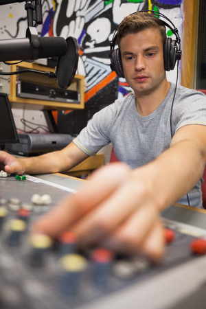 Handsome focused radio host moderating turning up volume in studio at college photo