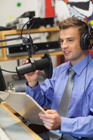Well dressed happy radio host moderating sitting in studio at college photo