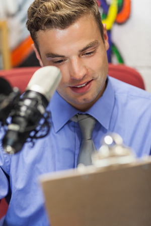 fm: Well dressed smiling radio host moderating holding clipboard in studio at college