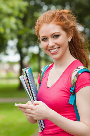 Gorgeous cheerful student holding notebooks texting on campus at college photo