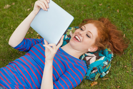 Gorgeous cheerful student lying on grass using tablet on campus at college photo