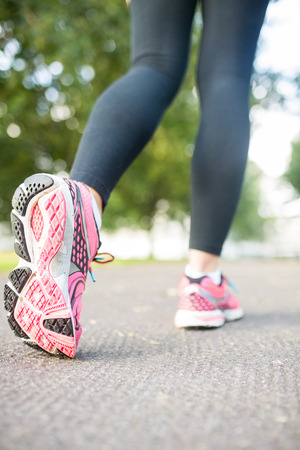 Close up picture of pink running shoes on a path in the park photo