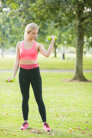 Active focused blonde lifting dumbbells in a park on a sunny day photo