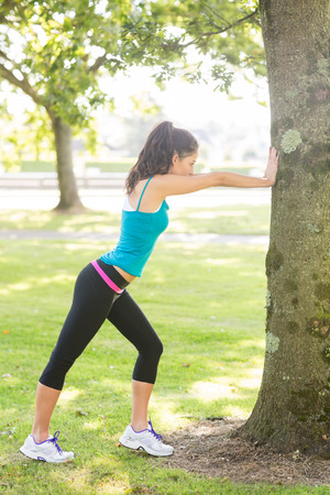 tied woman: Active beautiful brunette stretching her leg in a park on a sunny day Stock Photo