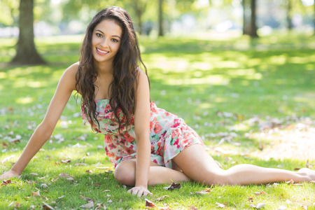 Stylish smiling brunette sitting on grass in a park on a sunny day photo