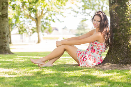 Stylish pretty brunette sitting under a tree in a park on a sunny day photo