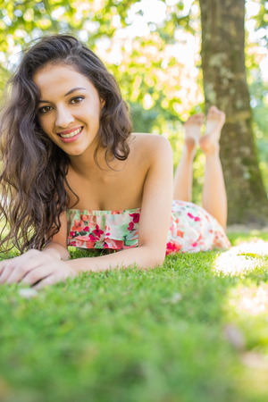 Stylish cheerful brunette lying on a lawn looking at camera in a park on a sunny day photo