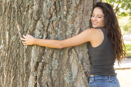 Casual attractive brunette embracing a tree with closed eyes in a park on a sunny day