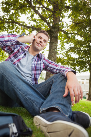 Handsome happy student sitting on grass phoning on campus at college Stock Photo