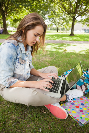 Pretty focused student sitting on grass using laptop on campus at college photo