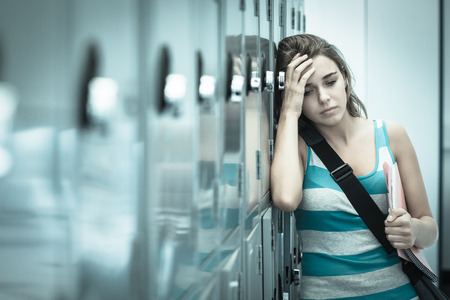 pounding head: Wincing pretty student having a headache in school