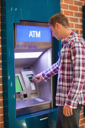 withdrawing: Handsome student withdrawing cash at an ATM Stock Photo