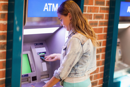 withdrawal: Pretty brunette student withdrawing cash at an ATM Stock Photo