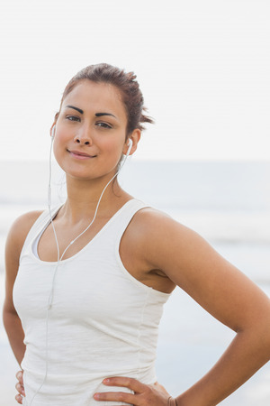 Portrait of a beautiful woman listening to music through earphones at beach photo
