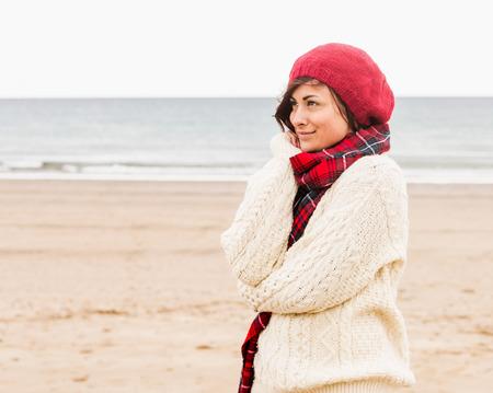 robo: Vista lateral de una mujer joven y bonita en ropa de abrigo con estilo que mira lejos en la playa Foto de archivo