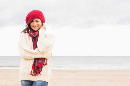 Portrait of a cute smiling young woman in stylish warm clothing on the beach photo