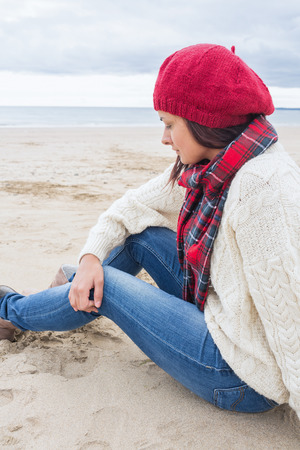 Side view of a young woman in stylish warm clothing sitting at the beach photo