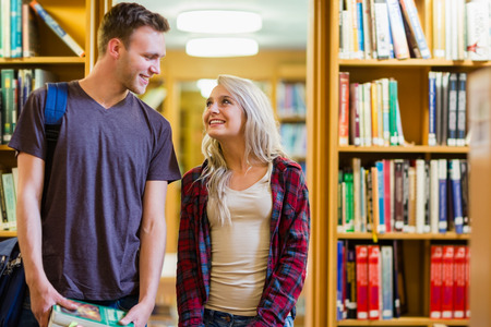 Smiling young couple look at each other in the library photo