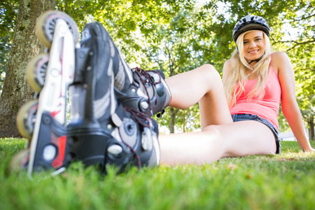 Casual attractive blonde wearing roller blades and helmet in a park photo