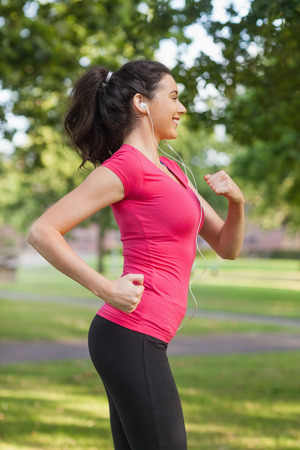 Happy sporty woman jogging in a park while listening to music photo