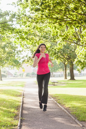 Gorgeous sporty woman jogging in a park while listening to music photo