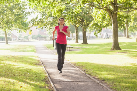 Sporty woman running in a park while listening to music photo