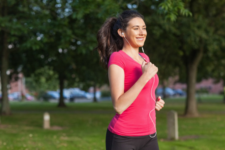 Motivated sporty woman running in a park listening to music photo