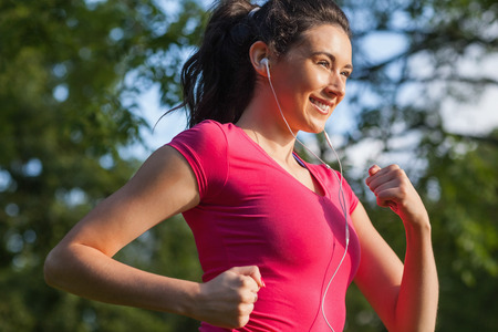 Cheerful young woman jogging in a park while smiling and listening to music photo