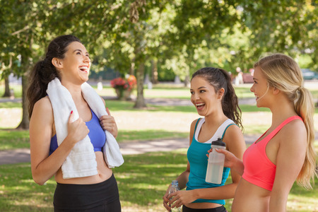 Three pretty sporty friends chatting in a park photo
