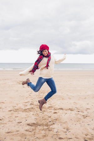 Full length of a woman in stylish warm clothing jumping at the beach photo