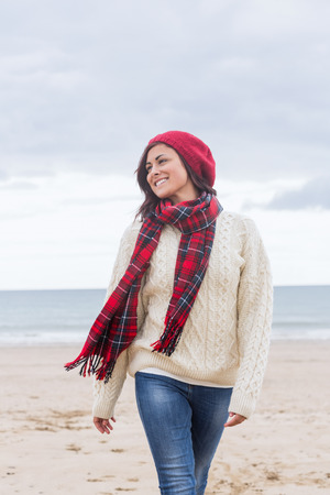 Pretty young woman in stylish warm clothing at the beach photo