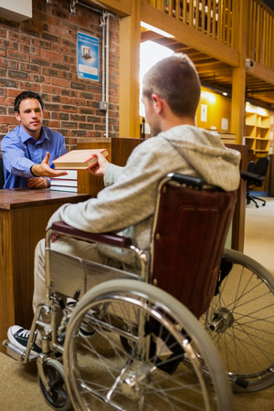 Male student in wheelchair at the counter in college library photo