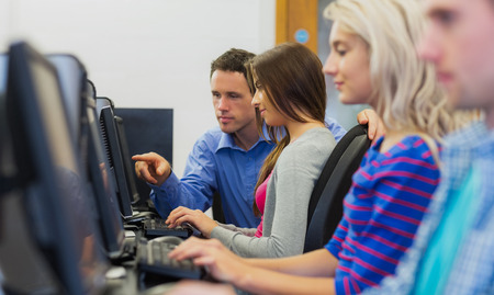 Side view of teacher showing something on screen to student in the computer room photo