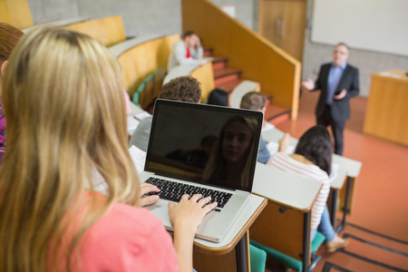 casuals: Rear view of a female using laptop with students and teacher at the college lecture hall