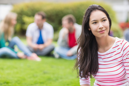Smiling young college student with blurred friends sitting in the park photo