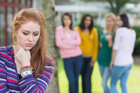 social outcast: Female student being bullied by other group of students